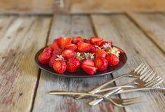 Fresas maduras y dulces en una placa negra en una tabla de madera Foto de archivo