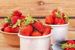 Fresas orgánicas rojas maduras en una placa y tazas del metal contra Fotografía de archivo