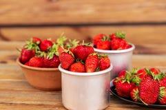 Fresas orgánicas rojas maduras en una placa y tazas del metal contra Imagen de archivo