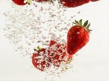 Fresas que caen en agua Fotos de archivo libres de regalías