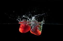 Fresas que salpican en el agua Fotos de archivo