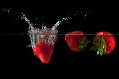 Fresas que salpican en el agua Fotografía de archivo