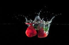 Fresas que salpican en el agua Foto de archivo libre de regalías