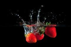 Fresas que salpican en el agua Imagen de archivo