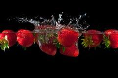 Fresas que salpican en el agua Foto de archivo