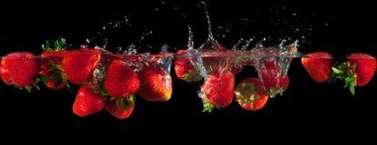 Fresas que salpican en el agua Imagen de archivo libre de regalías