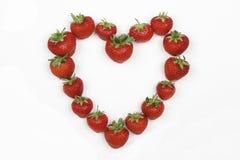 Fresas rojas en la dimensión de una variable de un corazón del amor Fotografía de archivo