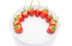 Fresas rojas en la placa blanca con el fondo blanco Foto de archivo