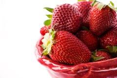 Fresas rojas en la placa y el fondo blanco imagen de archivo libre de regalías