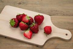 Fresas rojas en tabla de cortar de madera Fotografía de archivo