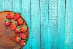 Fresas rojas frescas en placa de cerámica en el tablero de la mesa de madera de la turquesa Imágenes de archivo libres de regalías