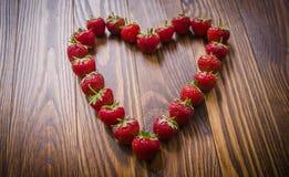 Fresas rojas frescas que mienten en forma del corazón Visión superior Foto de archivo