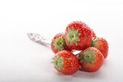 Fresas rojas hermosas en una cuchara de plata, contra el fondo blanco imagen de archivo
