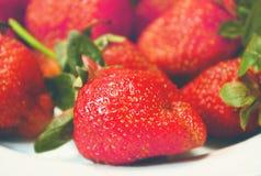 Fresas rojas jugosas en una placa blanca Fotografía de archivo