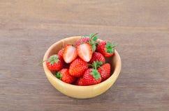 Fresas rojas maduras en cuenco de madera en la tabla de madera Imagen de archivo
