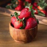 Fresas sabrosas frescas en cuadrado rústico de madera del fondo del cuenco de madera Imagen de archivo libre de regalías