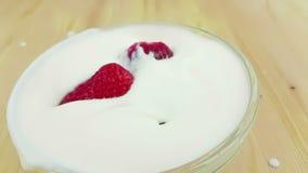 Fresas sanas que caen abajo en la cámara lenta adentro al yogur blanco en la tabla de madera, concepto de comida sana metrajes