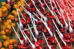 Fresas, sandías y frutas frescas del níspero en tazas plásticas Foto de archivo libre de regalías