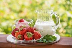 Fresas, un jarro de leche y yogur en un fondo verde Imagen de archivo