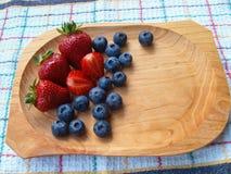 Fresas y arándanos en cuenco de madera en la toalla de cocina Imagen de archivo
