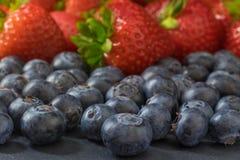 Fresas y arándanos que mienten en una tabla de piedra oscura Fotografía de archivo