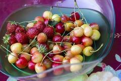 Fresas y cerezas en bol de vidrio Fotos de archivo libres de regalías
