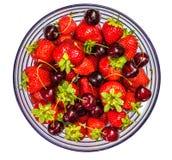 Fresas y cerezas en un bol de vidrio imagen de archivo
