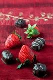 Fresas y chocolates en fondo rojo Imagen de archivo