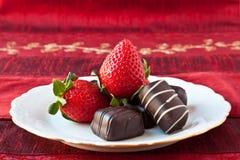 Fresas y chocolates en una placa foto de archivo libre de regalías
