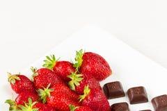 Fresas y pedazos de chocolate en el plato blanco aislado en el fondo blanco Ciérrese encima de la visión Imagenes de archivo
