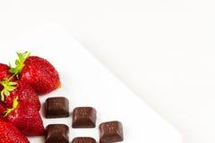 Fresas y pedazos de chocolate en el plato blanco aislado en el fondo blanco Ciérrese encima de la visión Imagen de archivo libre de regalías