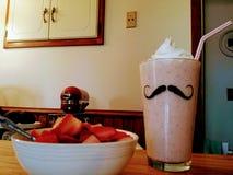 Fresas y Smoothie poner crema Fotografía de archivo