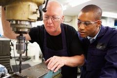 Fresatrice di uso di Teaching Apprentice To dell'ingegnere Immagine Stock Libera da Diritti