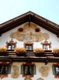 Fresco above windows with white curtains and wooden balcony in Oberammergau in Germany Royalty Free Stock Photos