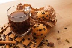 Fresco, apenas las magdalenas cocidas con las semillas del chocolate, del canela y del café fije con la taza de café oscuro Imagen de archivo libre de regalías