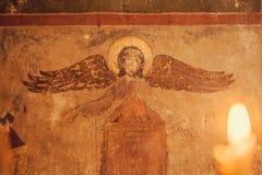 Fresco con ángel ciego en iglesia cristiana antigua y luz de la vela Símbolos religiosos Imágenes de archivo libres de regalías