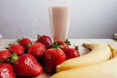 Fresco del smoothie del plátano de la fresa mezclado en la tabla de madera Fotografía de archivo libre de regalías