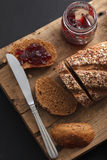 Fresco entero del grano y del atasco del pan oscuro del multigrain cocido en rústico Foto de archivo libre de regalías