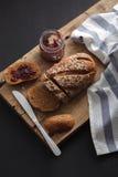 Fresco entero del grano y del atasco del pan oscuro del multigrain cocido en rústico Fotos de archivo libres de regalías