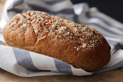 Fresco inteiro da grão do pão escuro do multigrain cozido em rústico Fotos de Stock