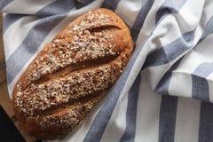 Fresco inteiro da grão do pão escuro do multigrain cozido em rústico Foto de Stock Royalty Free