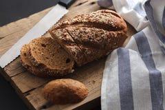 Fresco inteiro da grão do pão escuro do multigrain cozido em rústico Fotografia de Stock Royalty Free