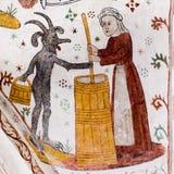 Fresco medieval de una mantequilla de batido de la mujer con el diablo foto de archivo