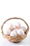 Fresco, ovos na cesta no fundo branco Imagens de Stock Royalty Free