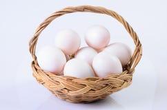 Fresco, ovos na cesta no fundo branco Imagens de Stock
