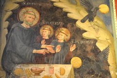 Fresco of Saint Benedict, Saint Maurus and Saint Placidus. Saint Benedict with young Maurus and Placidus.  The fresco can be found at the San Benedetto Monastery Stock Image