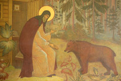 Fresco with Saint Sergius and bear on the entrance of Trinity Sergius Lavra. Stock Photo