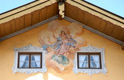 Fresco between windows with white curtains in Oberammergau in Germany. Hoto made in Oberammergau in Bavaria (Germany). The picture shows the upper part of the Royalty Free Stock Photos
