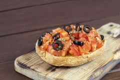 Freselle,or friselle dried bread, italian food. Friselle or Freselle Italian appetizer on wooden board with tomatoes, garlic,black olives, oregano, salt, and stock photography