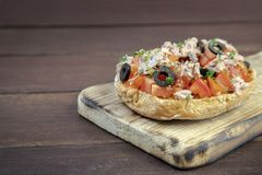 Freselle,or friselle dried bread, italian food. Friselle or Freselle Italian appetizer on wooden board with tomatoes, tuna, garlic,black olives, oregano, salt royalty free stock photography